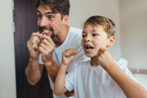 dad and son flossing after learning about Ellis Dental