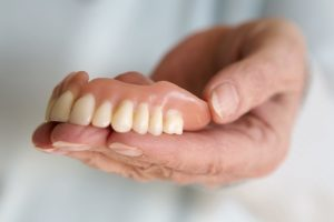 an example of removable dentures in Fort Worth TX in someones hand